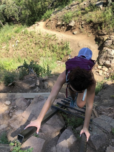 Woman climbing the ladder on the Saddle Rock Trail